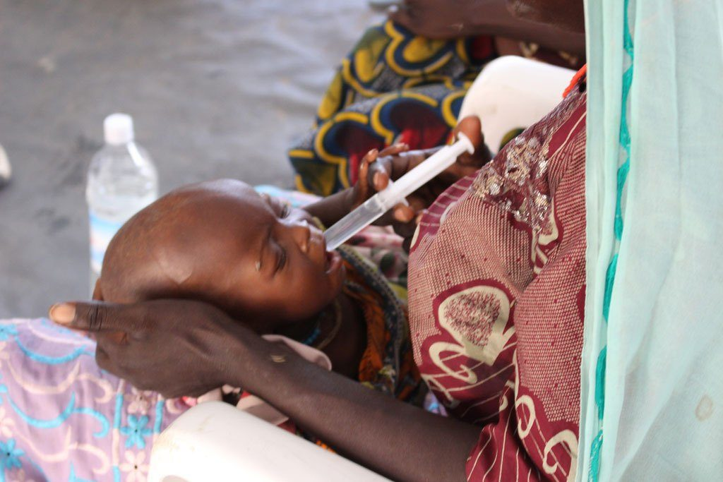 A severely malnourished child receives treatment in a clinic in Banki, north-east Nigeria. He is receiving water with sugar and food supplements to increase his body weight.  Photo: OCHA/O.Fagan