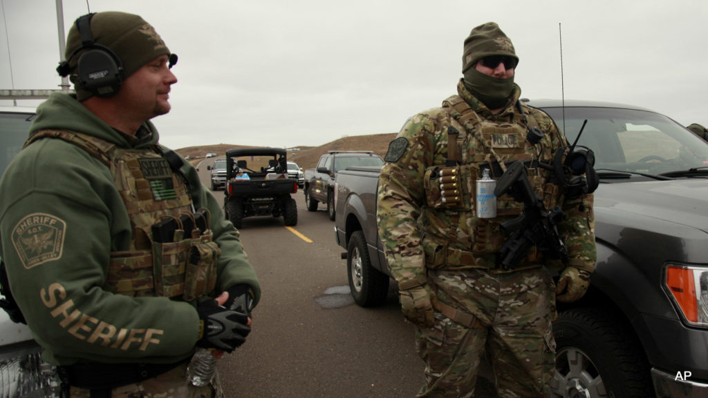 Members of the Stutsman County SWAT watch protesters demonstrating against the Dakota Access Pipeline near the Stand Rock Sioux Reservation, as they stand next to a police barricade on Highway 1806 in Cannon Ball, N.D., Sunday, Oct. 30, 2016.