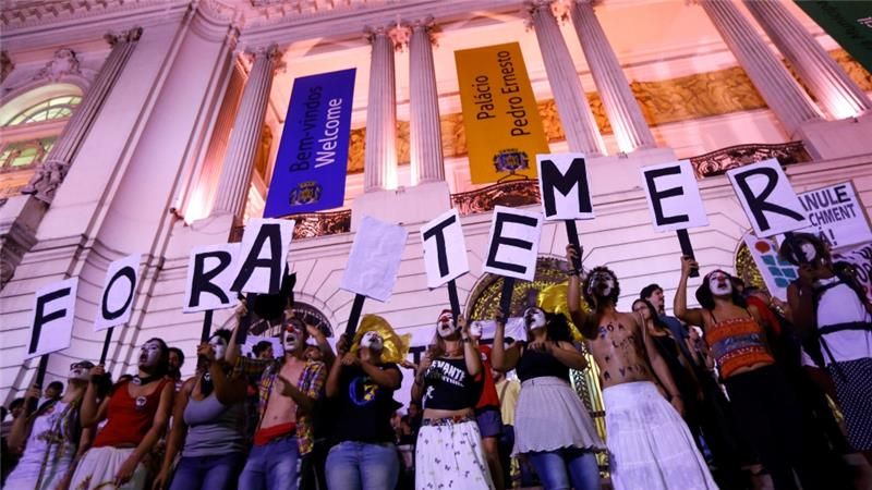 "Protesters in Rio de Janeiro hold placards against Brazil's President Michel Temer, which read ""Out Temer"" [Reuters]"