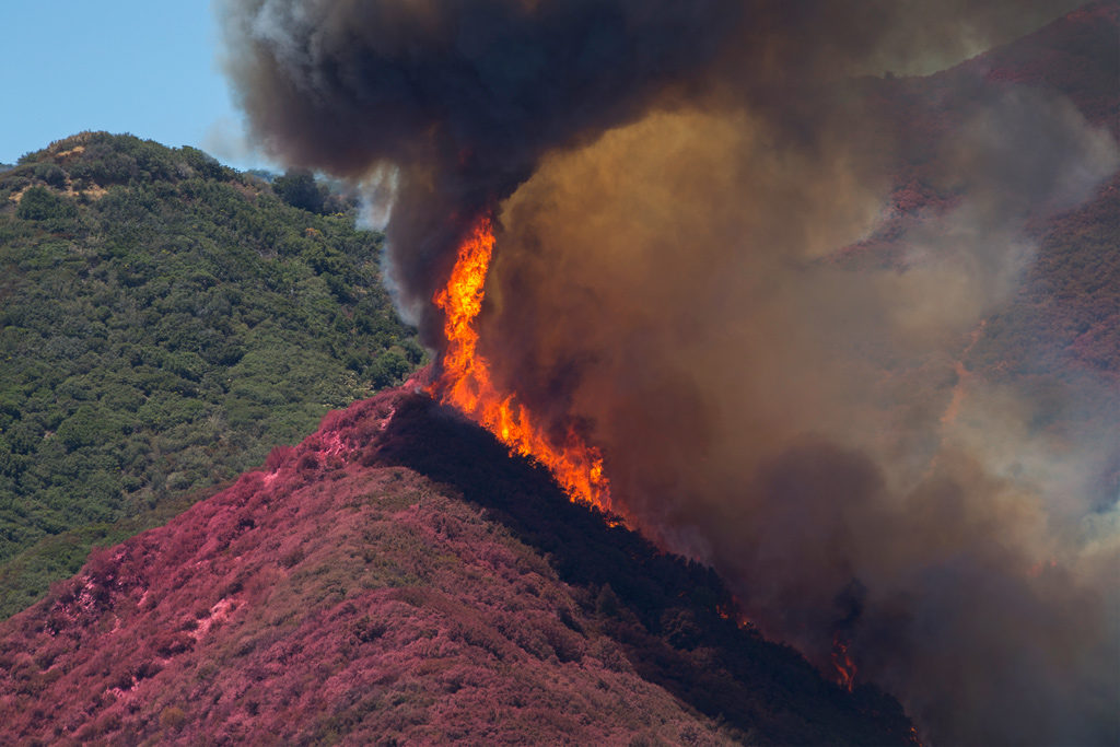 Flames threaten to jump a ridge that firefighting aircraft have painted red with fire retardant above Cajon Boulevard at the Blue Cut Fire on Aug. 18, 2016, near Wrightwood, California. Photo: David McNew/Getty Images
