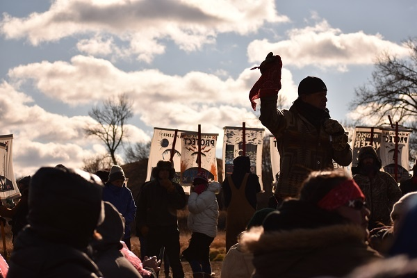 Red Fawn's uncle speaks before a crowd holding the red scarf his niece gave him. | Photo: Priya Handa
