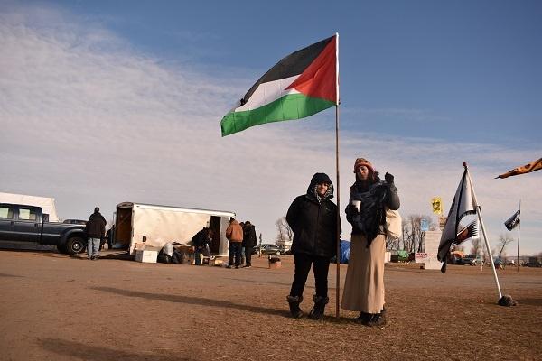 Megan and Nadya in front of the Palestinian flag. | Photo: Priya Handa