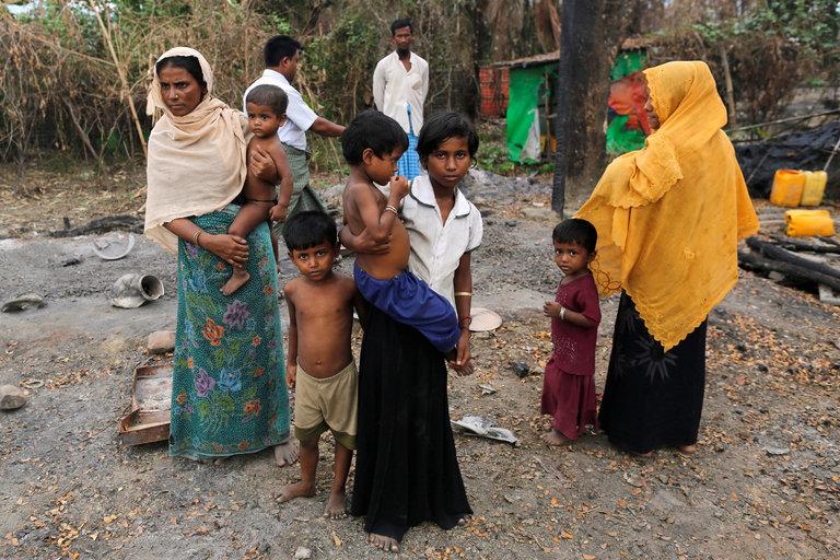 A family outside a market destroyed by fire, in a Rohingya village in Myanmar, in October. Credit Soe Zeya Tun/Reuters