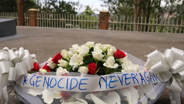 "A bouquet of flowers tied with a ribbon showing the message ""Genocide Never Again."" Photo: Reuters"