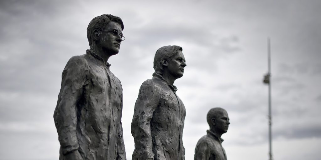 """""""Anything to Say?"""" is a bronze sculpture and art installation by Italian sculptor Davide Dormino, representing, from left, whistleblowers Edward Snowden, Julian Assange, and Chelsea Manning next to the U.N. offices in Geneva on Sept. 15, 2015."""