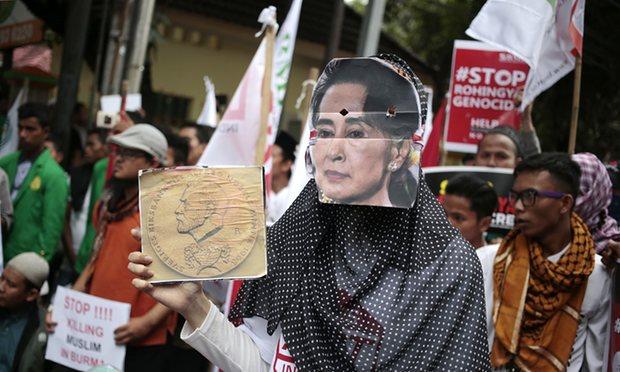 A Muslim woman wears an Aung San Suu Kyi mask during a rally against the persecution of Rohingya. Photograph: Dita Alangkara/AP