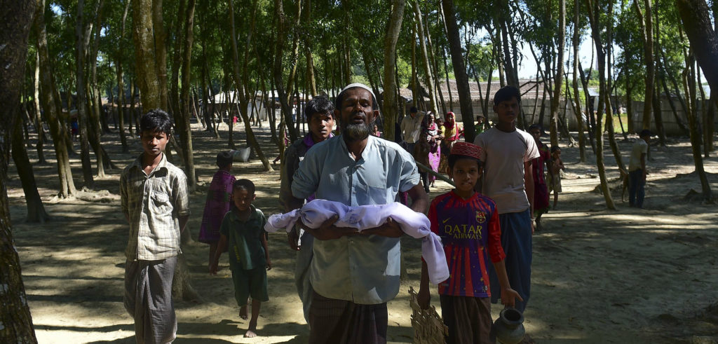 A Rohingya refugee from Burma carries the body of a six-month-old boy who died in a Bangladeshi refugee camp on November 26. MUNIR UZ ZAMAN/AFP/Getty Images
